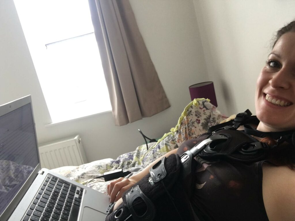 Sinead sat wearing back brace on laptop.