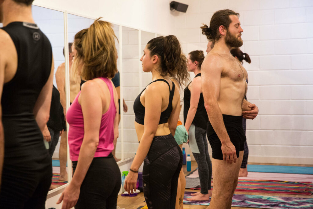 A Yogafurie hot yoga class with male instructor Aaron leading a standing meditation