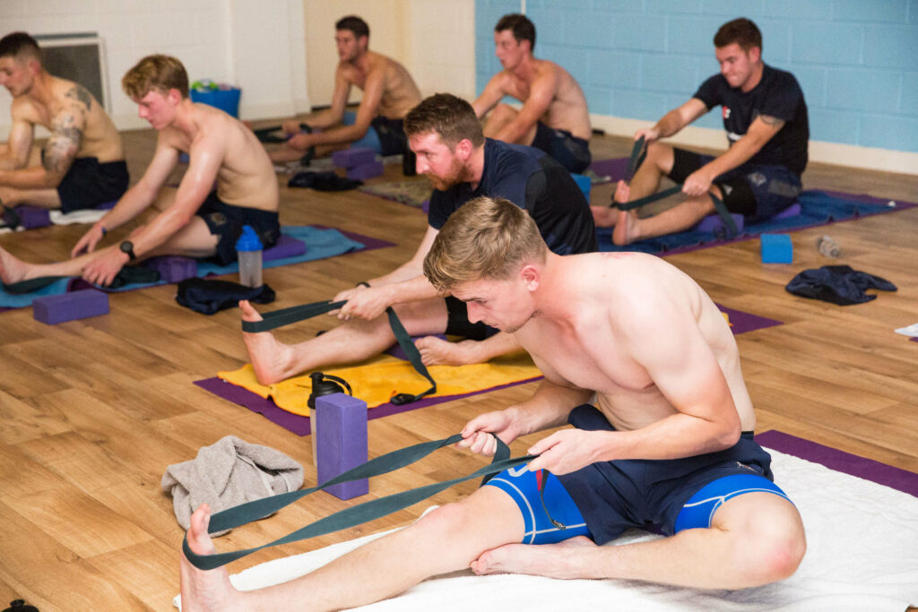 Determined cricketers use a strap to carry out a hamstring stretch