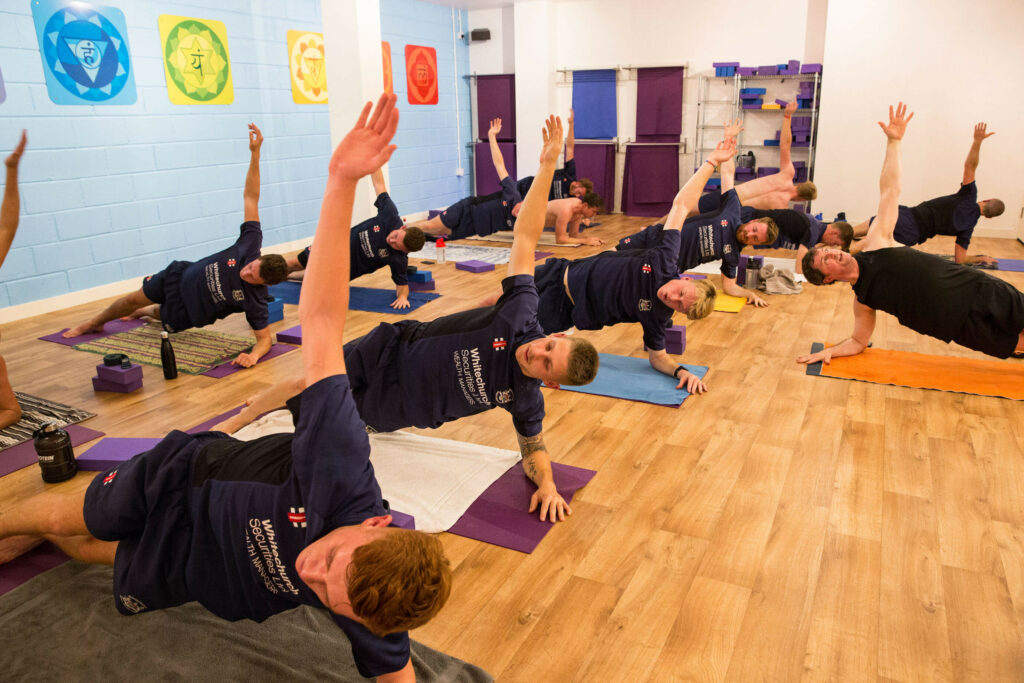 Cricketers carry out a side plank pose as part of their training at Yogafurie