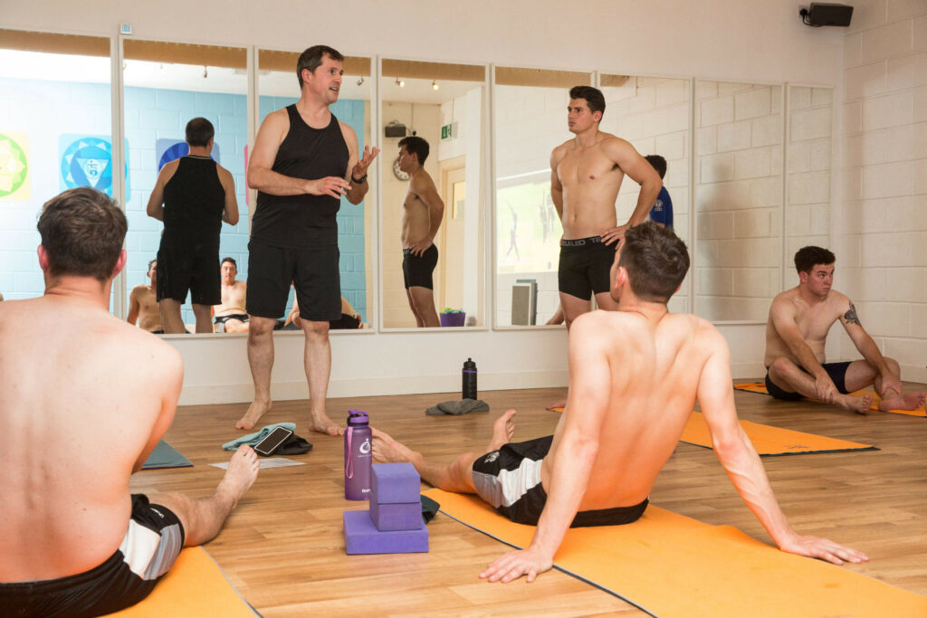 Lead Instructor Ed explains concept to professional cricketers in hot yoga training session at Yogafurie