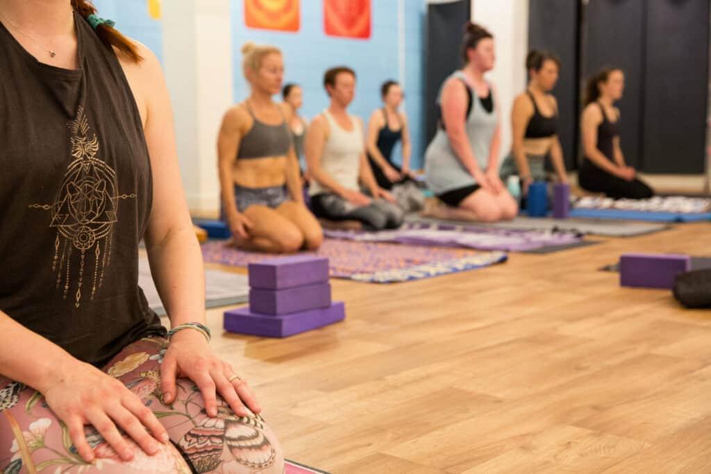 students kneeling in meditation hands on thighs