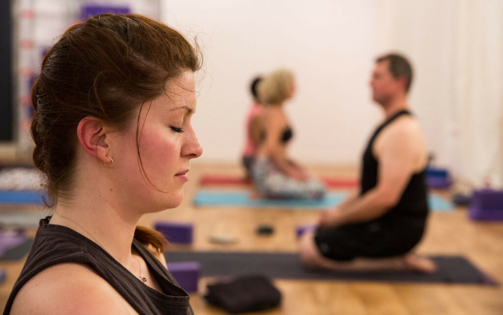 Resting and meditating during a hot yoga class with eyes closed