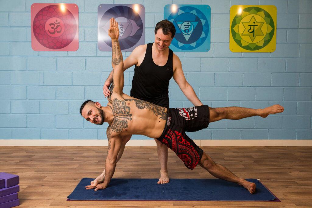 Ed assisting yoga student Mario to do a challenging side plank pose