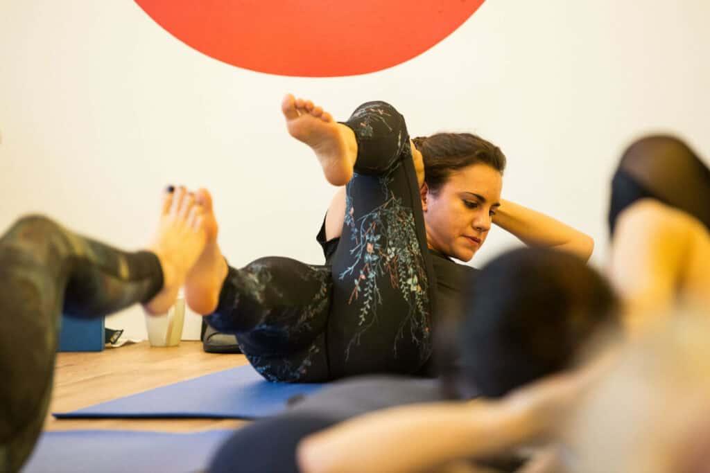 teacher training Lisa yoga doing twisted boat core exercise