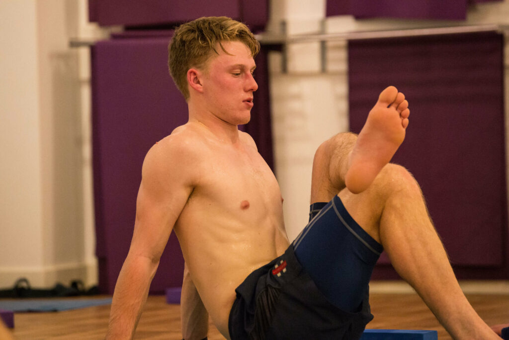 Male yoga student and professional cricketer practicing a hot yoga hip and glute stretch
