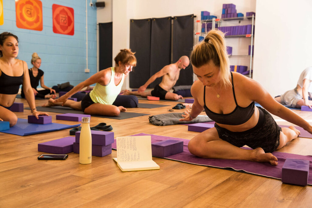 Yoga class where people are doing pigeon pose with arms back challenging but sat down