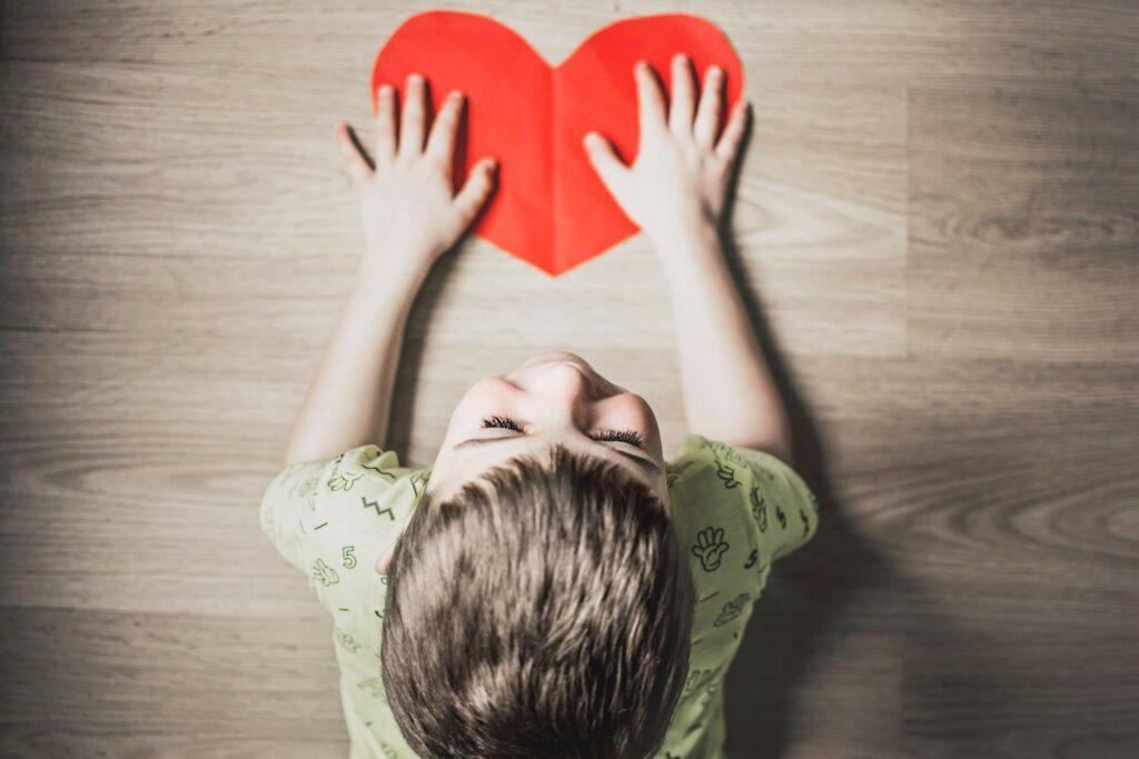 Giving your heart to something, child holding a paper heart