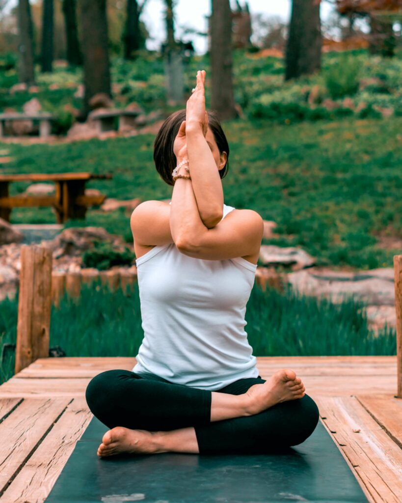 Woman practicing yoga seated eagle arms with firelog legs relaxing in a forest