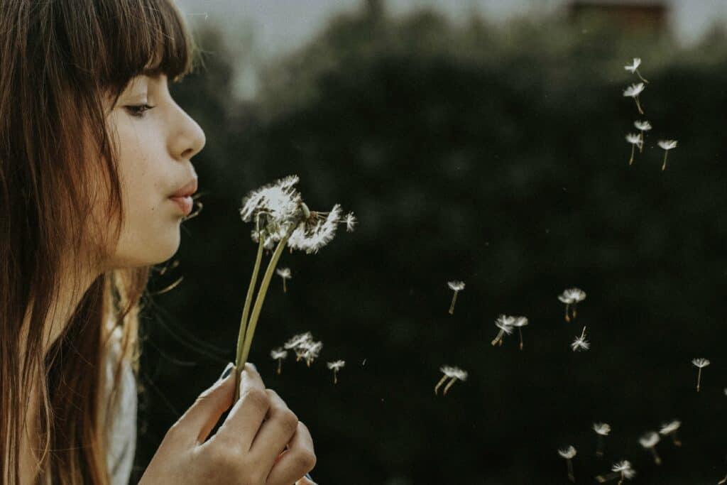 Woman breathing onto flowers