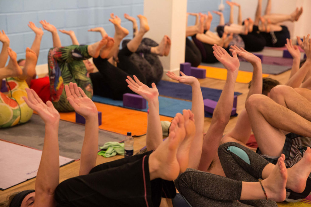 Yoga students practising on their backs during a popular hot yoga class at Yogafurie