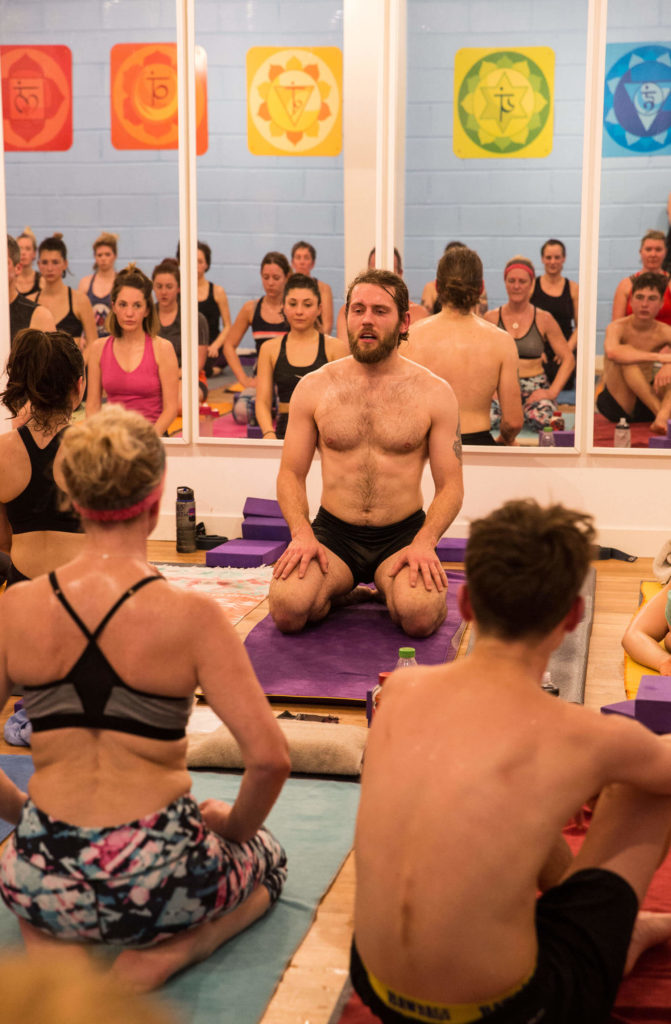 Yogafurie teacher Aaron in the hot yoga studio addressing the students