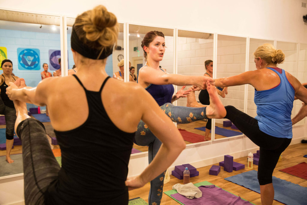 Yogafurie students in hand to foot balancing pose with teacher Sinead