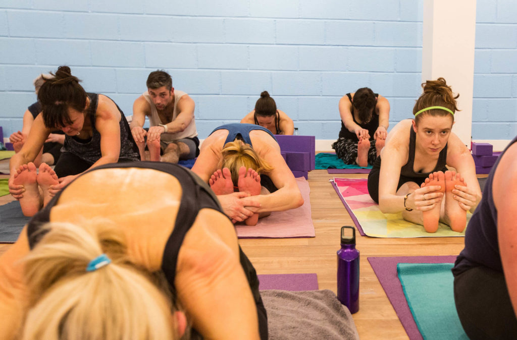 Students in a Yogafurie hot class doing a yin-style stretch for hamstrings