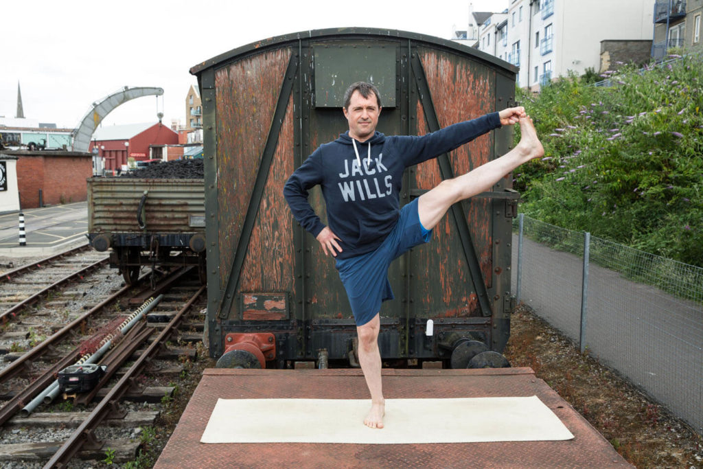 Yogafurie Lead Instructor Ed Wood demonstrates a balancing posture requiring good hip and hamstring flexibility