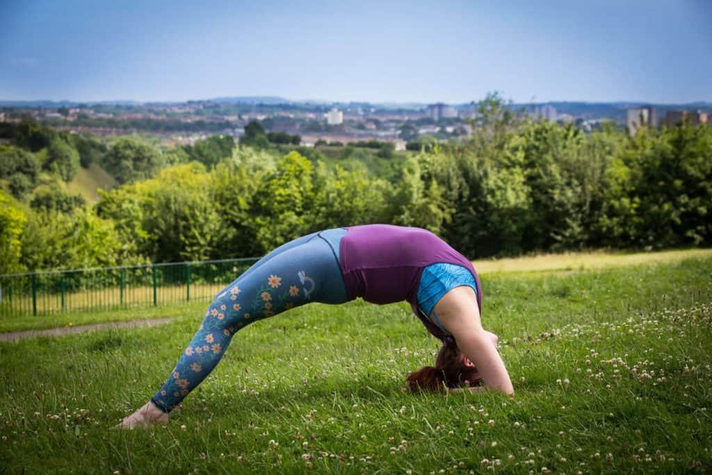 Yogafurie teacher Sinead practicing a backbend in a field over Bristol
