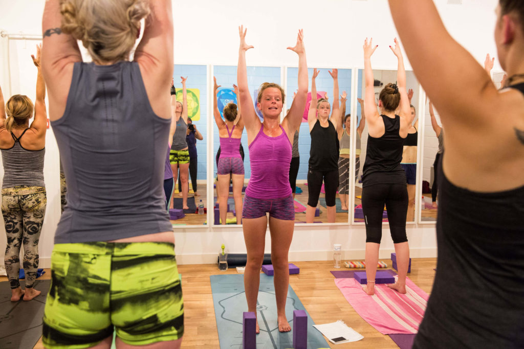 Yogafurie Teacher Trainee demonstrating good standing posture in a Yogafurie hot yoga class