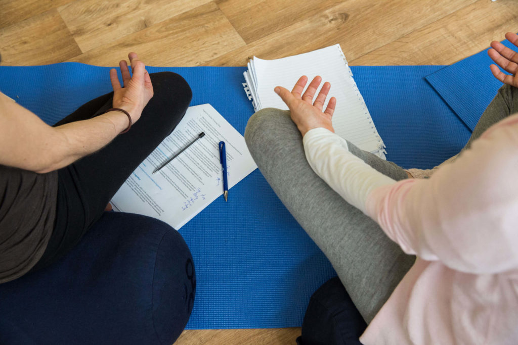 Students in a yogafurie class with notes in front of them during a meditation
