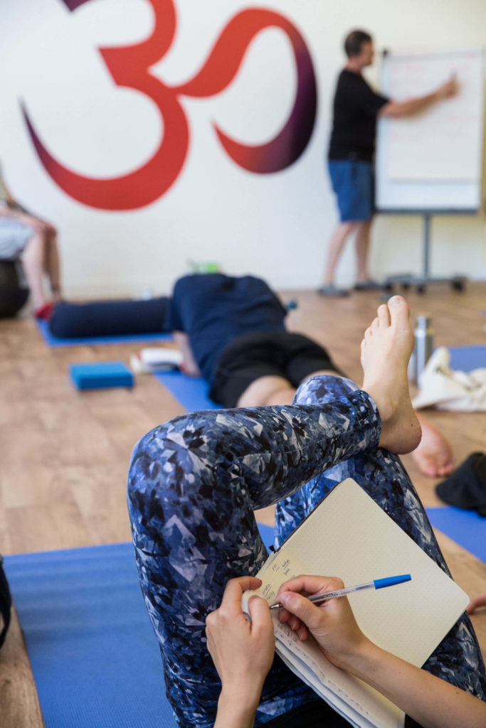 Teacher trainee taking notes in a philosophy session at Yogafurie.