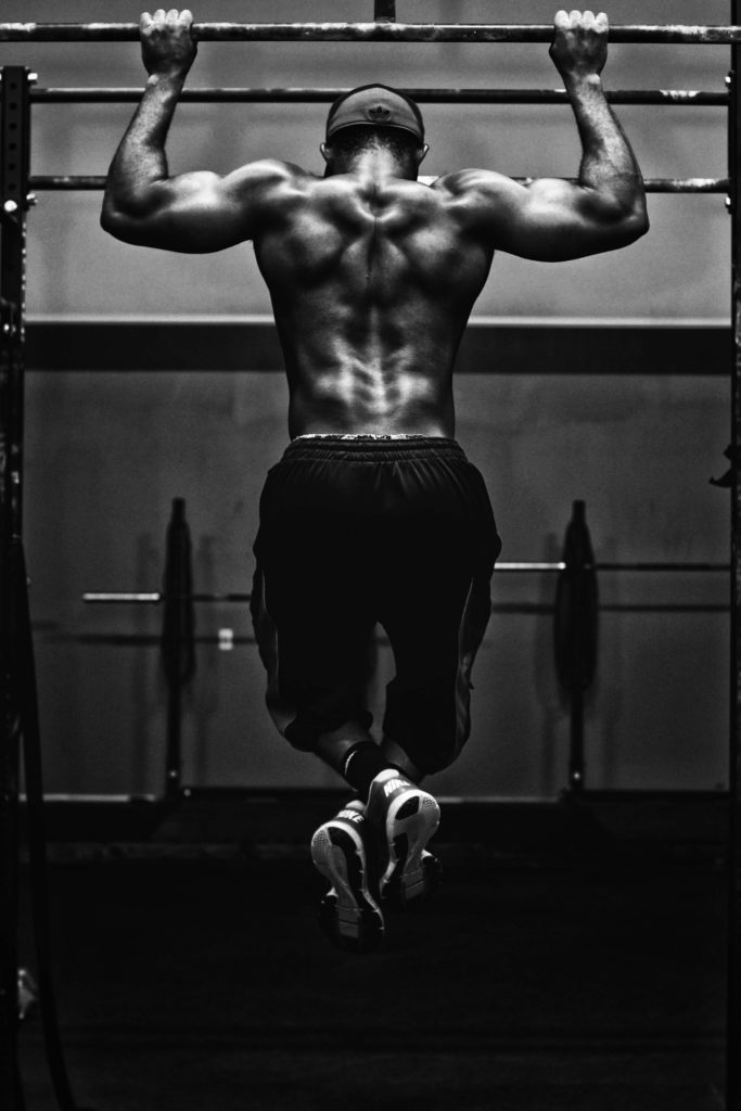 Man carrying out pull-ups, which rely heavily on the serratus anterior just below the armpits on the side of the body