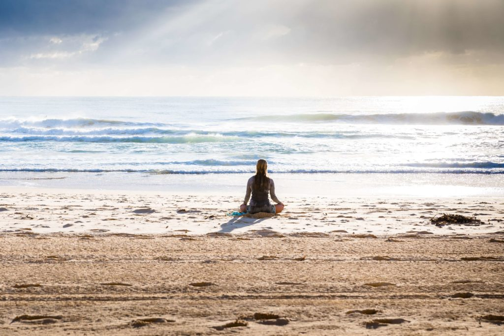 Person meditating on a beach looking out to sea