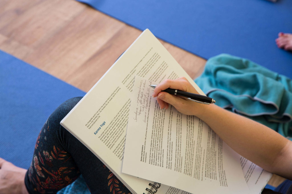 A trainee writing notes based on the Yogafurie Training Manual
