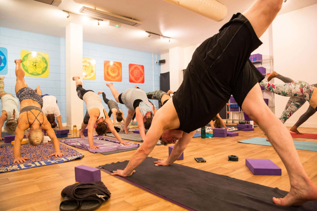 Ed teaching a yoga class at Yogafurie in downward dog pose with a leg lifted