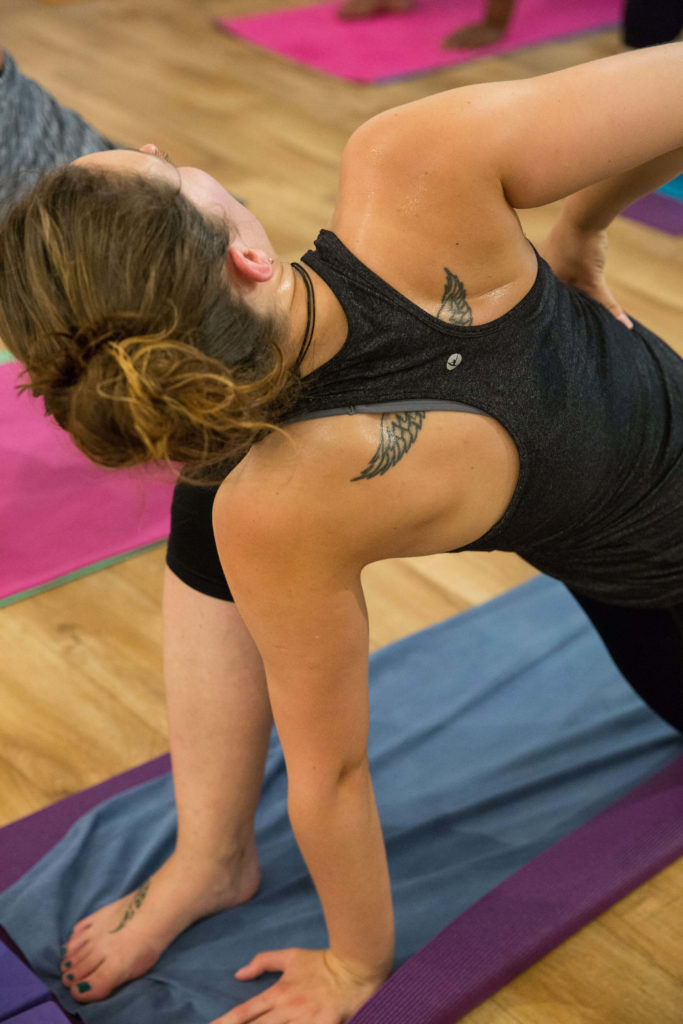 Hot yoga student at Yogafurie who is doing a gentle twist