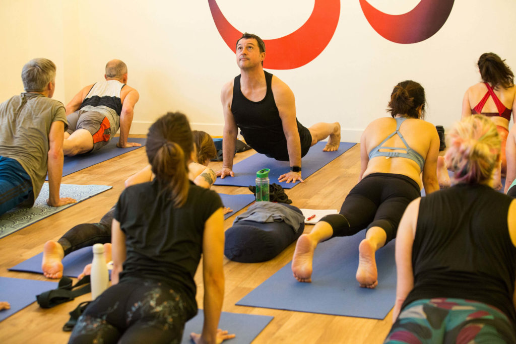 Ed teaching a group of trainees in upward facing dog