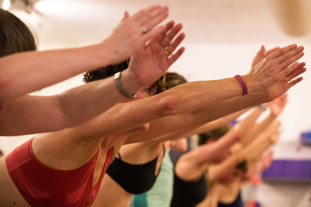 A yogafurie hot class where the students are performing a pose with their arms outstretched