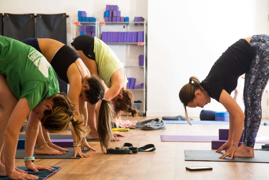 Yogafurie students doing a forward fold where it's common to need to use extra supports under the hands