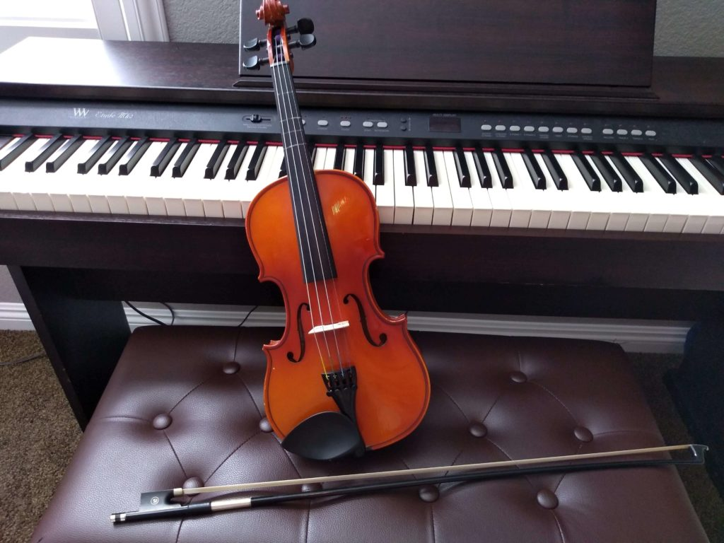 An unplayed piano and violin