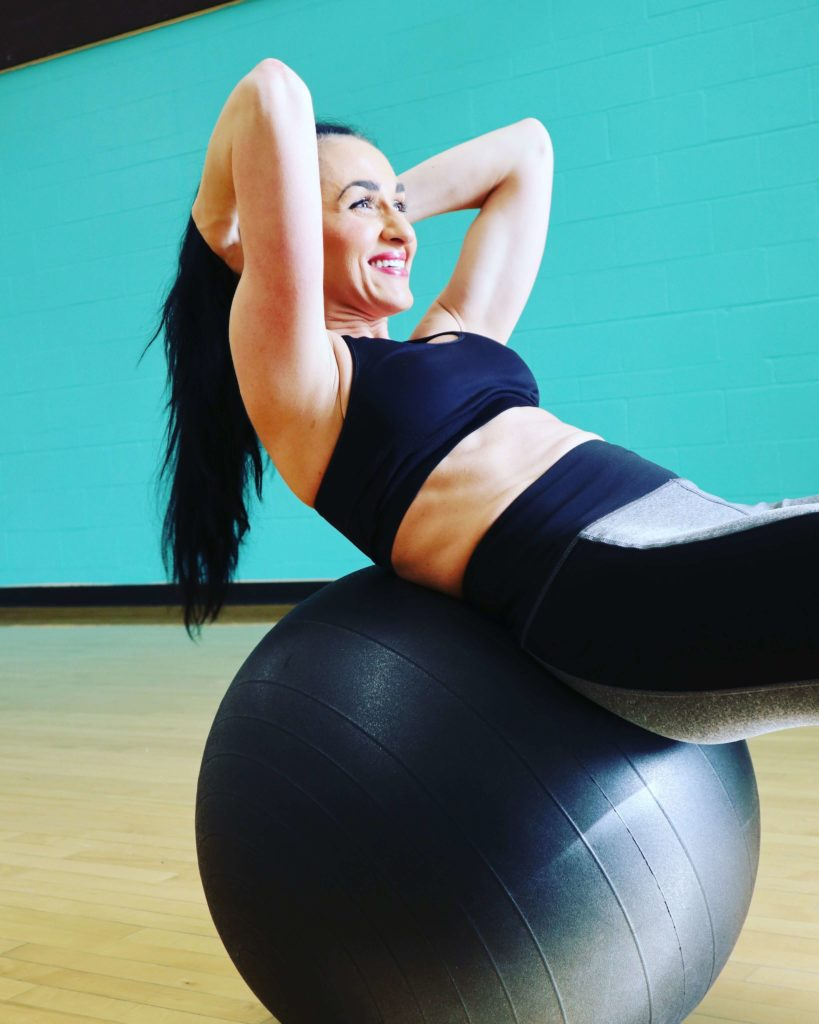 Woman carrying out another ab exercise on an inflatable ball