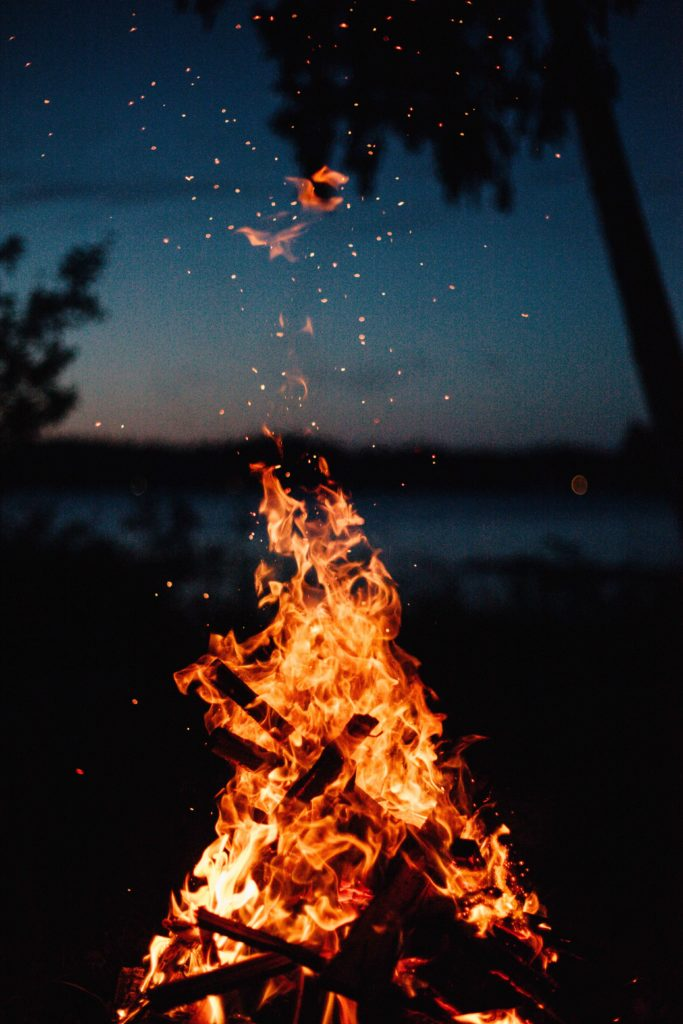 A wood fire burning with embers rising into the air
