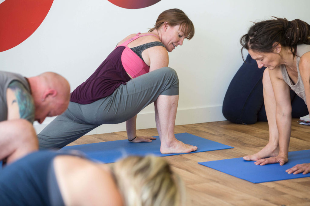 Morven teaching a yoga class in a forward lunge