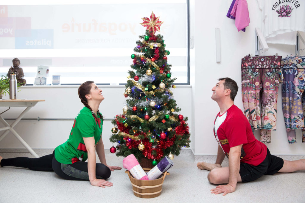 Ed and Sinead doing pigeon pose on either side of a Christmas tree
