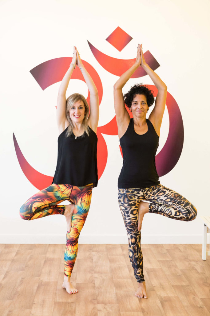 Yogafurie students demonstrate a version of tree pose with the palms together above the head