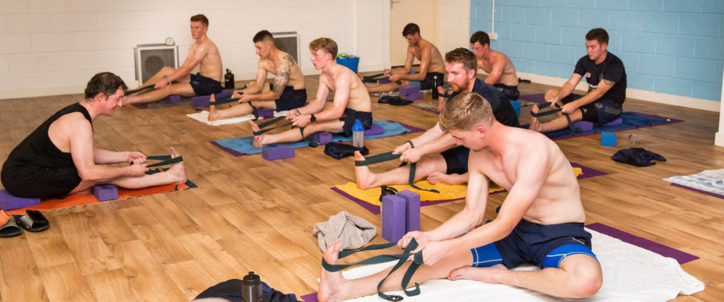 Gloucestershire County Cricket Team in class with Ed, in Janu Sirsasana assisted by bands.