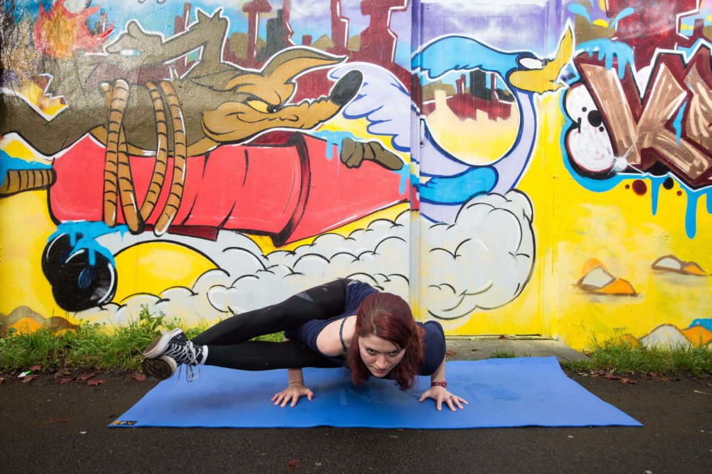 Sinead showing an arm balance where you stay low to the ground and bring your legs out to the side crossed at the ankle