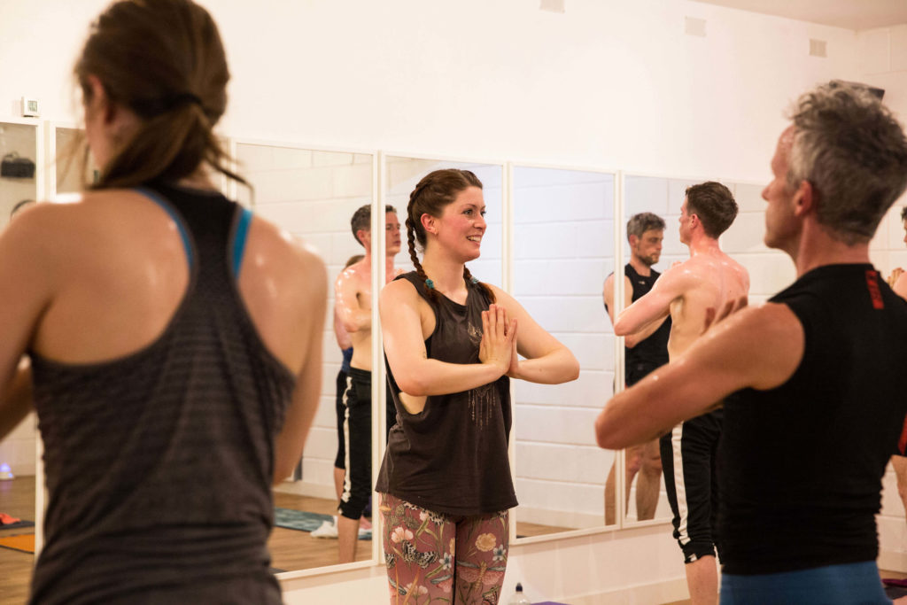 Sinead teaching Hot Yoga class, stood with hands at heart centre.