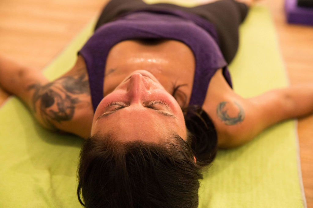 Woman lying down with eyes closed during a Yogafurie hot yoga class