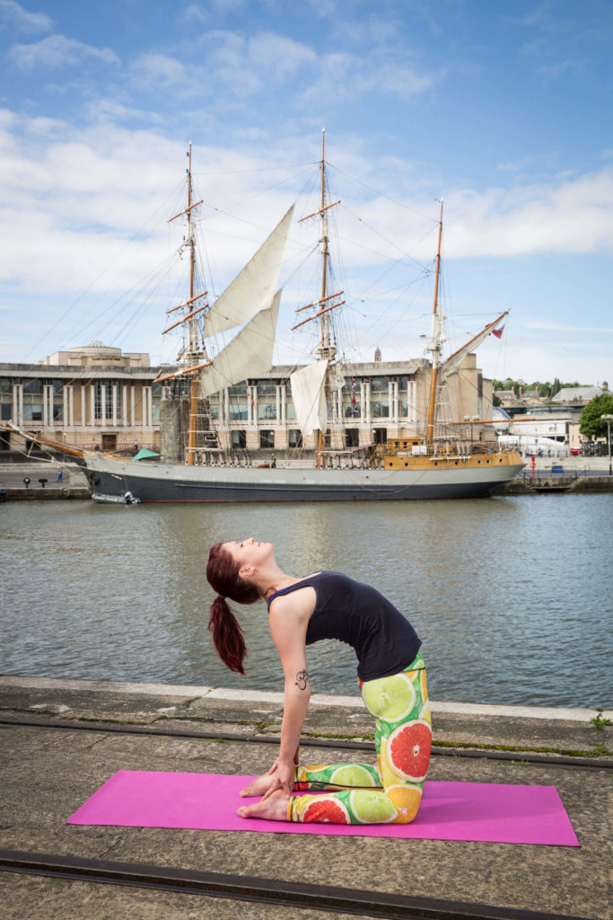 Sinead in Camel pose by the docks, ship in background.