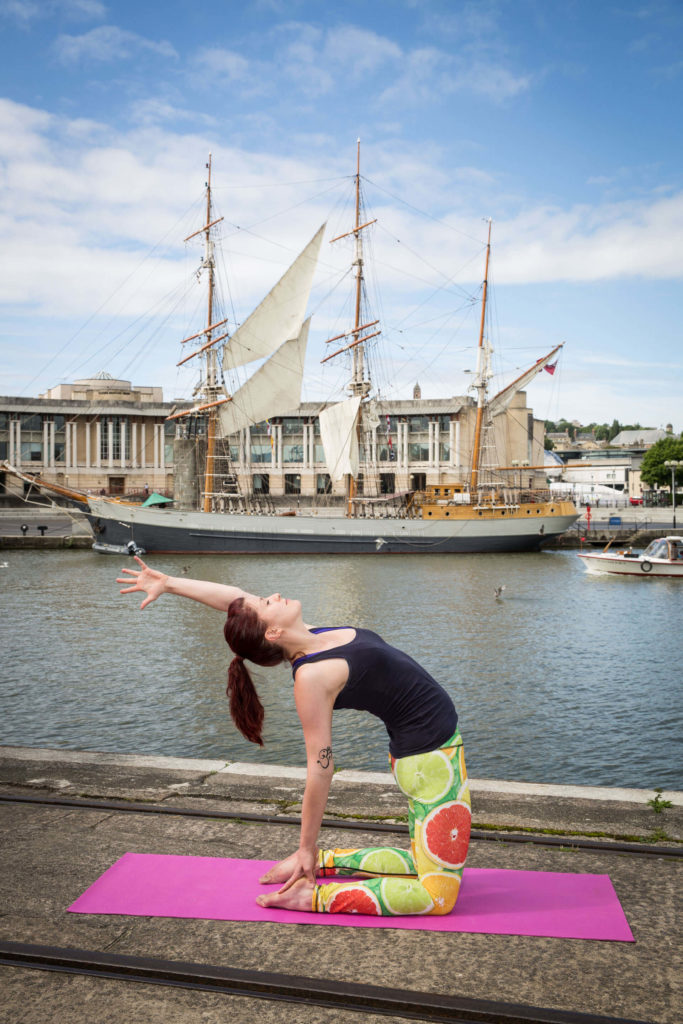 Sinead in Camel pose by the docks, lifting left hand off heel and extending behind the head.