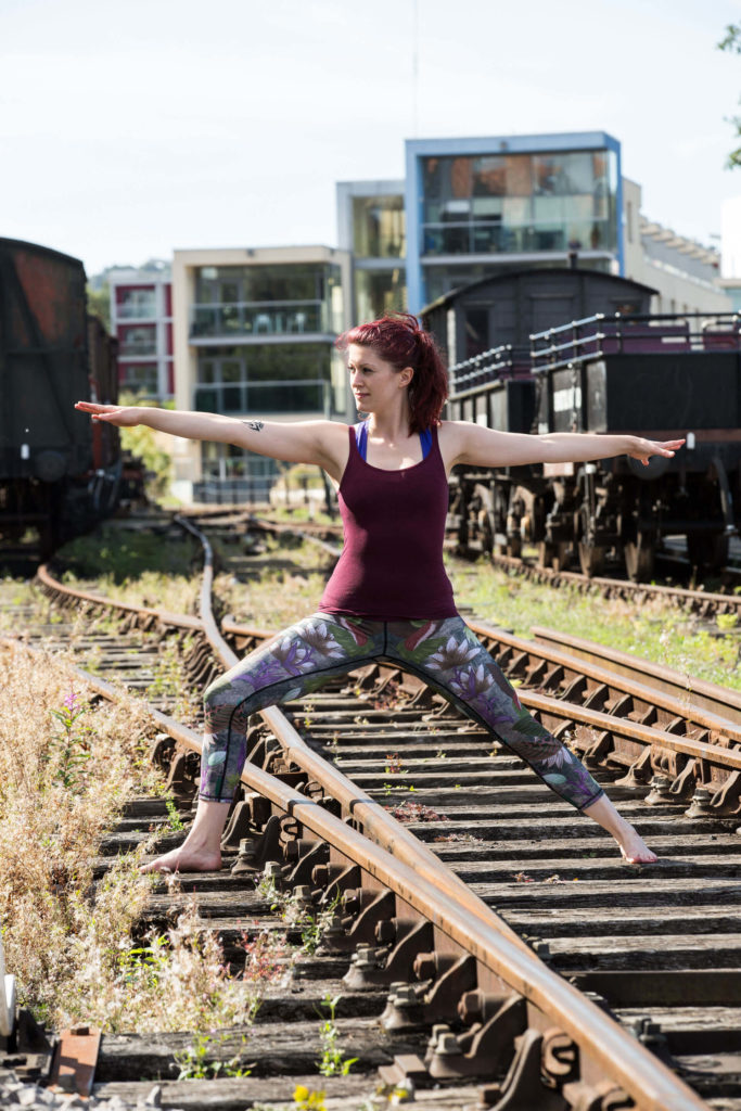 Sinead in Warrior 2 pose on the train tracks.