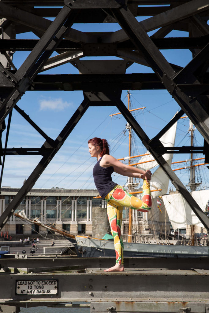 Sinead in Natarajasana at the docks with both hands holding foot, before  lifting right arm (step three).