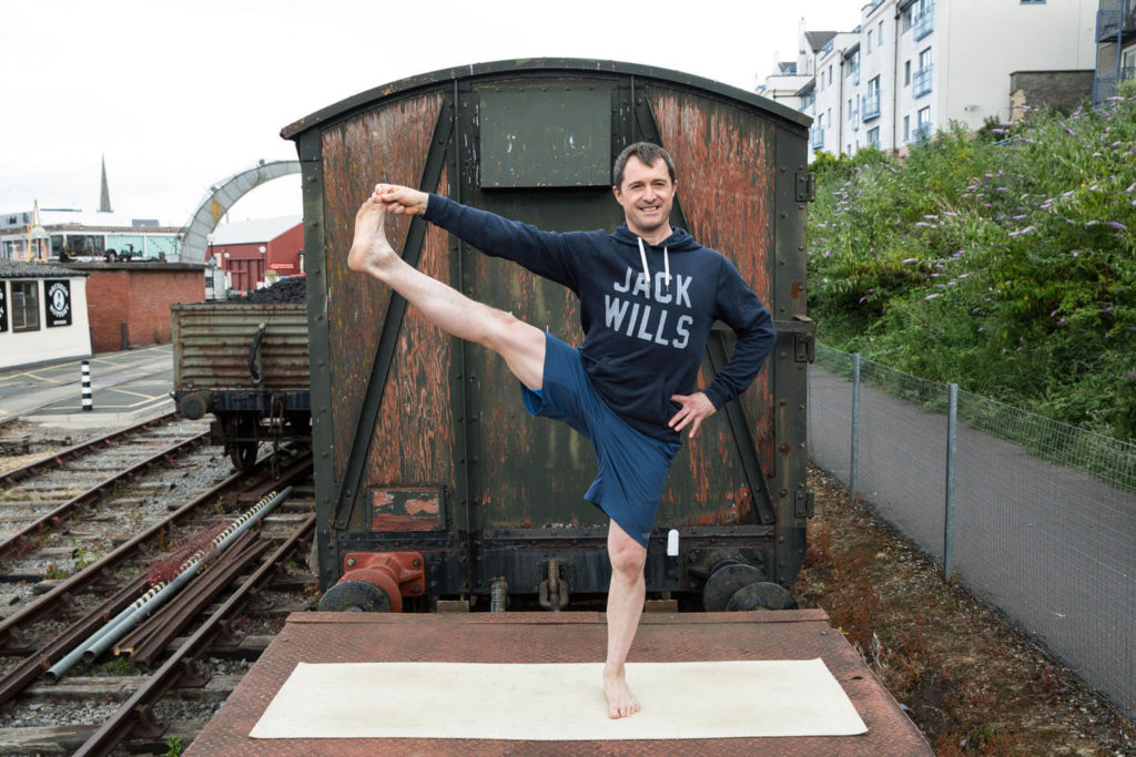 'Building on Tree Pose, Utthita Hasta Padangustasana challenges your leg and core strength, as well as your balance' - Ed in Utthita Padangustasana pose in front of old train carriage.