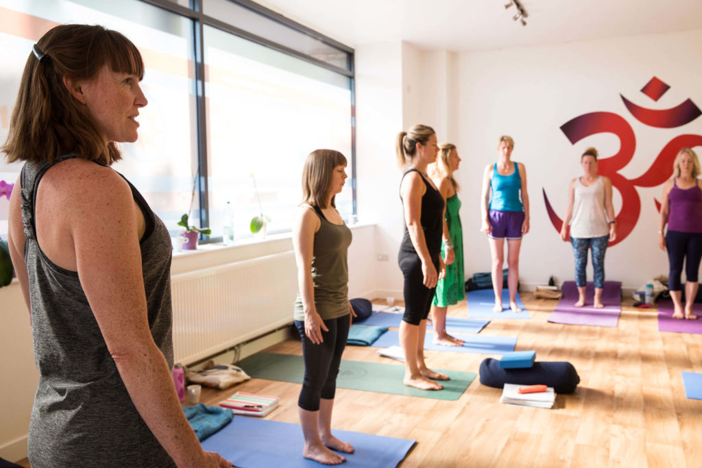 Teacher Trainees carry out mountain pose or tadasana with the hands by the sides of the hips