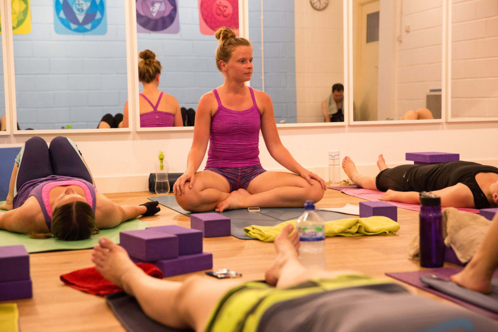 A yoga class meditating at Yogafurie