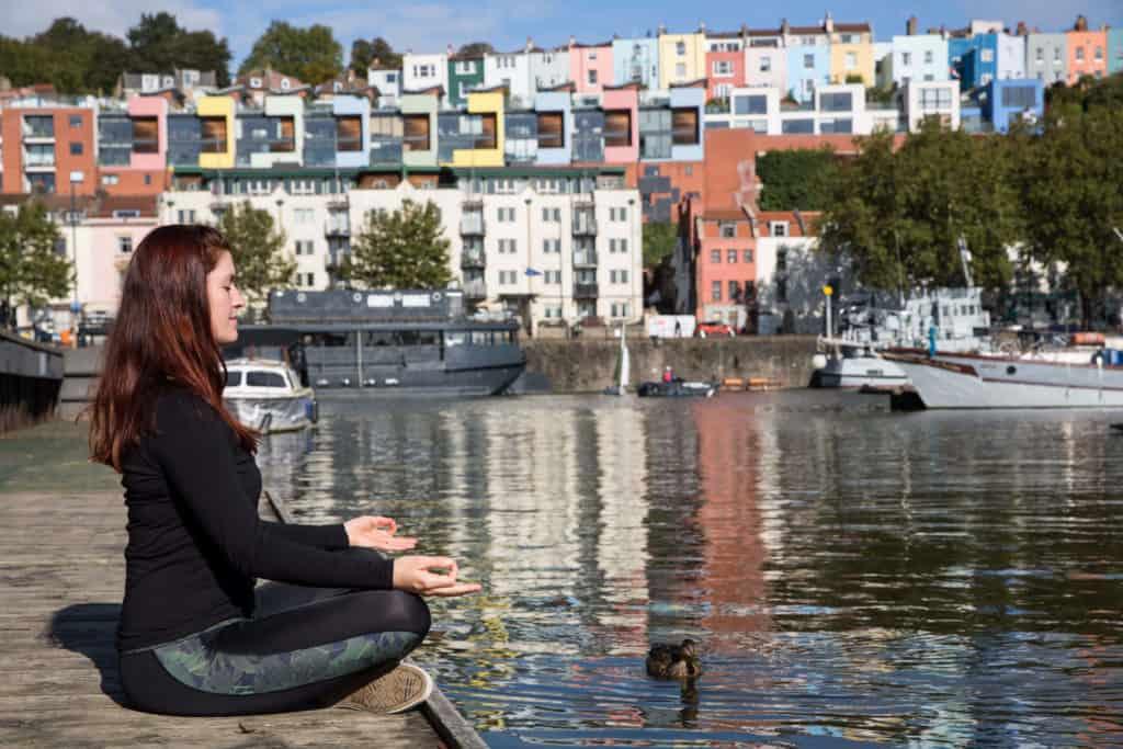 Sinead sitting in a meditation posture at Bristol harbourside