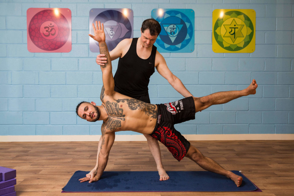 MMA Fighter Mario in Side Plank pose, assisted by Ed.